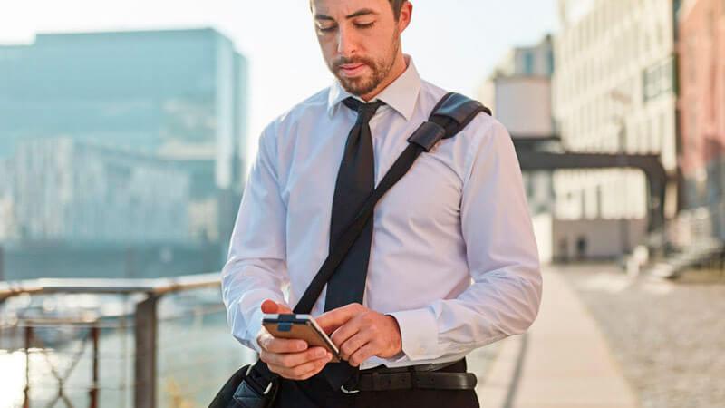 Mann arbeitet unterwegs mit Smartphone